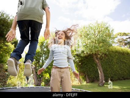 Kinder springen auf dem Trampolin im Garten - Stockfoto