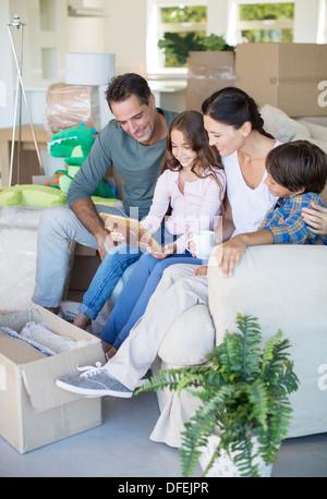 Familie betrachten Bilderrahmen auf Sofa unter Kartons - Stockfoto