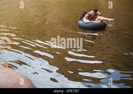 Paar spielen im Innenrohr in See - Stockfoto