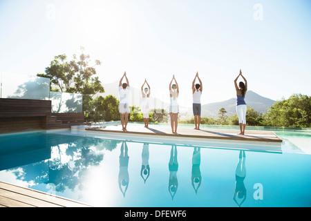 Menschen praktizieren Yoga am Pool - Stockfoto