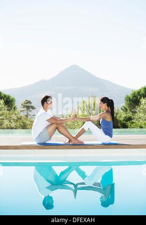Paar üben Yoga am Pool - Stockfoto