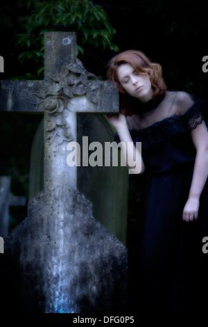 ein Mädchen im schwarzen Kleid auf einem Friedhof - Stockfoto