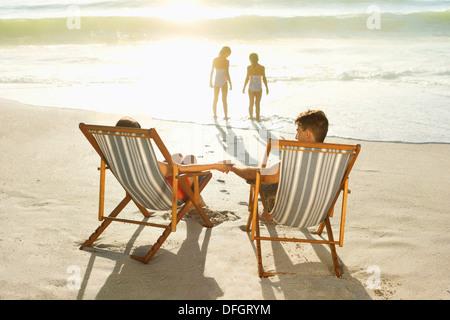 Eltern, die Töchter in der Brandung am Strand spielen beobachten - Stockfoto