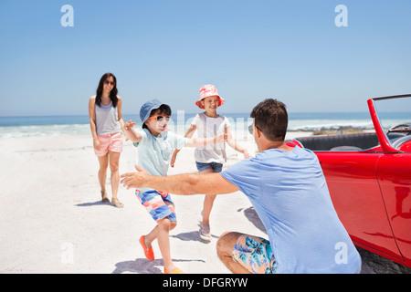 Vater erreichen um Kinder am Strand neben dem Cabrio zu umarmen - Stockfoto