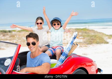 Vater und Kinder Lächeln im Cabrio am Strand - Stockfoto