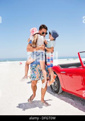 Vater umarmt Kinder am Strand neben dem Cabrio - Stockfoto