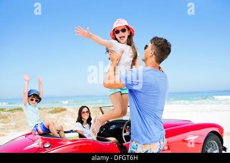 Anhebende Tochter Vater vom Cabriolet am Strand - Stockfoto