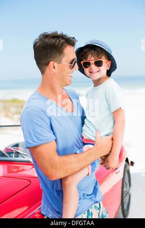 Vater und Sohn lächelnd am Strand neben dem Cabrio - Stockfoto