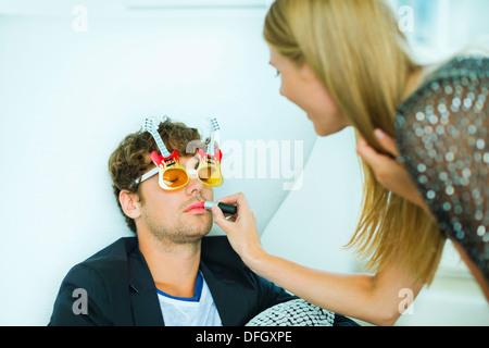 Frau Auftragen von Lippenstift zu schlafen Mann auf party - Stockfoto