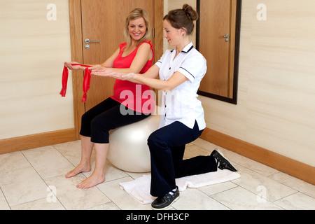 Ein Physiotherapeut zeigt eine lächelnde schwangere Mutter sitzt auf einer Yoga-Ball, wie Sie die Übung mit einem - Stockfoto