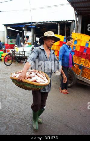 Der Mann mit müde Gesicht tragen Fische Korb in Fischmarkt in vertikalen Rahmen. 15. Juli 2013 - Stockfoto