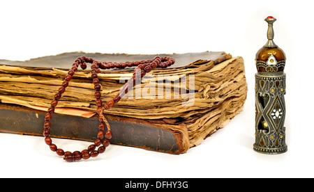 Koran, Gebetskette und alte Parfüm-Flasche auf weißem Hintergrund - Stockfoto