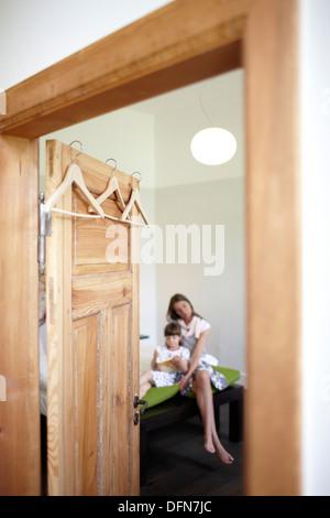 Mutter und Tochter sitzen auf einem Hotelbett, Fincken, Mecklenburg-Western Pomerania, Deutschland - Stockfoto
