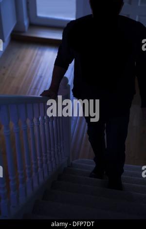 Drohende Gefahr als Silhouette eines Mannes geht eine dunkle Treppe. - Stockfoto