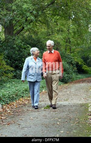 Älteres kaukasischen paar einander betrachtend und hand in hand gehen durch den Wald, verschwommen grünen Hintergrund, - Stockfoto