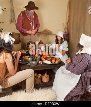 Reenactment-Szene des ersten Thanksgiving-Dinner in Plymouth 1621 mit einer Pilger-Familie und ein Wampanoag Indianer - Stockfoto