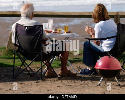 Älteres Paar mit einem BBQ auf einer Klippe mit Blick auf den Strand, Widemouth Bay, Cornwall, UK - Stockfoto