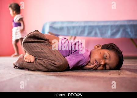 Kleine Indianerjunge auf einem Steinboden in einem indischen Dorfhaus schlafen. Selektiven Fokus. - Stockfoto