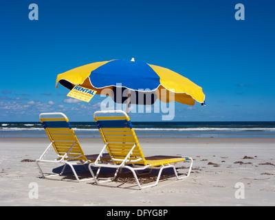 Liegestühle und Sonnenschirm zur Vermietung in Daytona Beach, Florida - Stockfoto