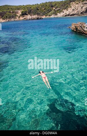 Frau im Wasser an einem Strand in Portinatx, Ibiza, Balearen, Spanien - Stockfoto