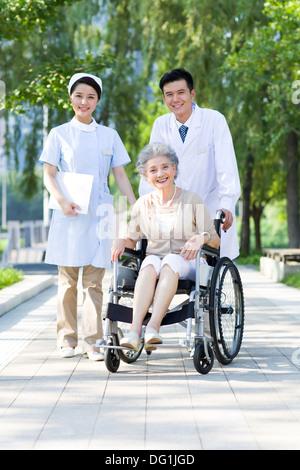 Arzt, Krankenschwester und Rollstuhl gebundenen Patienten - Stockfoto