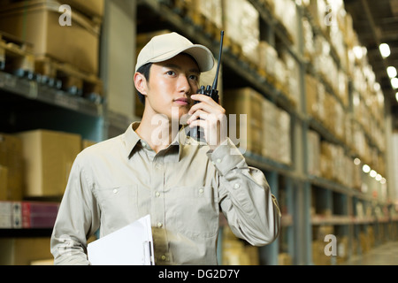 Junge Logistikmitarbeiter mit Walkie-talkie im Lager - Stockfoto