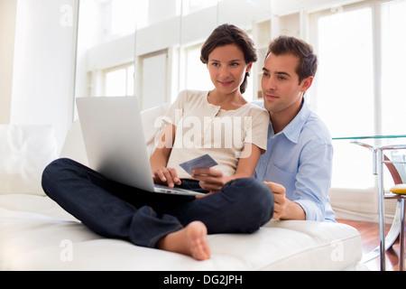 Frau Mann Laptop indoor Computer Internet Sofa im Wohnzimmer - Stockfoto