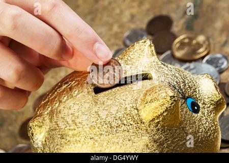 Horizontale Foto weibliche Finger, die einzigen Cent Inbetriebnahme Sparschwein mit Münzen herumliegen auf Stein - Stockfoto