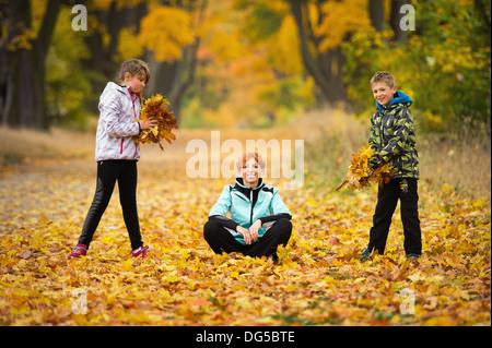 Mutter mit Kindern im Park spielen im Herbst - Stockfoto