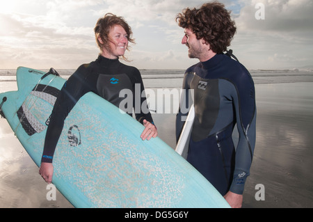 paar am Strand mit Surfbrettern stehend, hat man eine Gopro Kamera Surfbrett - Stockfoto
