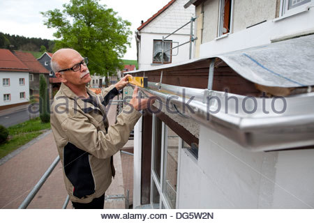 Senior woman Überprüfung des Regens fließt von seinem Haus, Bucheloh, Thüringen, Deutschland - Stockfoto