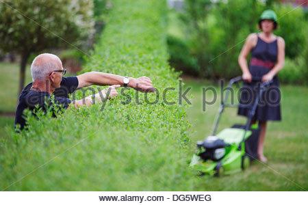 Senior woman zeigt Zeit, eine Frau mit Rasenmäher - Stockfoto