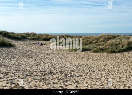 Eine Familie Unterstände genießt die Einsamkeit einer Sanddüne in alten Hunstanton. - Stockfoto