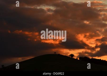 zwei Menschen zu Fuß auf dem Ivinghoe Beacon Hill mit Regenwolken & Sonnenuntergang - Stockfoto
