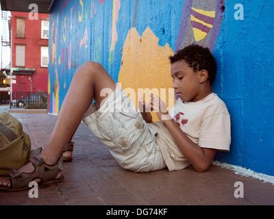 Junge, halb verlegen, halb sitzen auf dem Boden einer fröhlich bemalte Wand. - Stockfoto