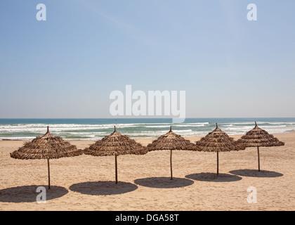 Blauen Himmel als Hintergrund und Reihe von Stroh Sonnenschirme am Strand am Meer. - Stockfoto