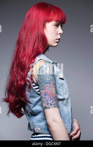 Junge Frau mit langen roten Haaren und Tattoos, Profil - Stockfoto