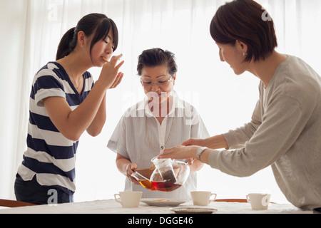 Drei-Generationen-Familie Tee gießen - Stockfoto