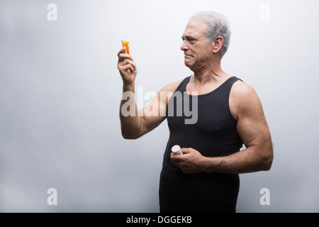 Senior woman Tablettenfläschchen betrachten - Stockfoto