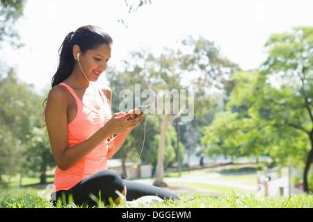 Junge Frau anhören von MP3-Player im park - Stockfoto