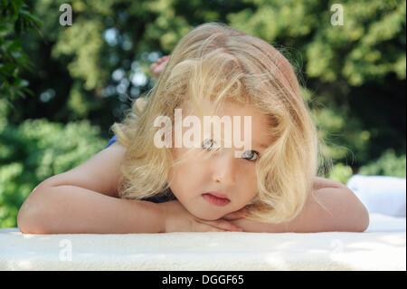 Kleines Mädchen liegend auf einer Decke, front Ansicht - Stockfoto