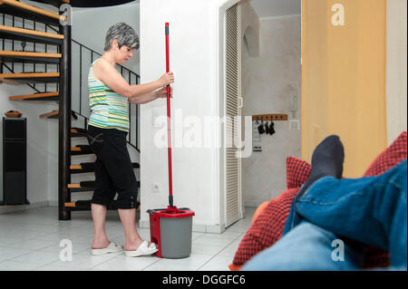 Frau, Reinigung, während ein Mann auf der Couch liegt - Stockfoto