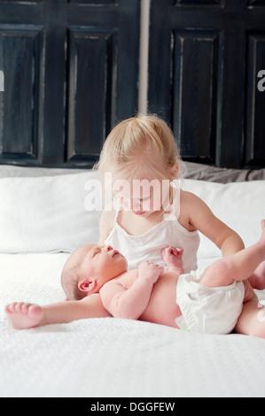 Mädchen mit kleinen Bruder am Bett sitzen - Stockfoto