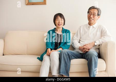 paar sitzen auf dem sofa weibliche blonde haare aus gesicht tragen rosa kariertes hemd braun. Black Bedroom Furniture Sets. Home Design Ideas