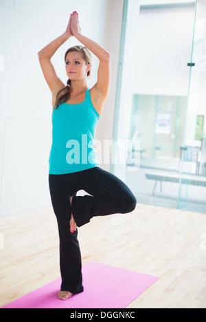 Junge Frau auf Yoga-Matte in Baum-Lage - Stockfoto