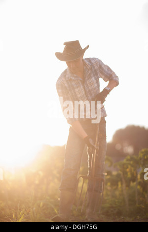 Junger Mann arbeitet auf Hof in der Sonne - Stockfoto