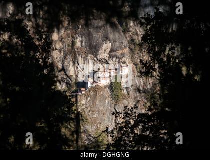 Taktsang Palphug Kloster (Tiger Nest) eingerahmt von Wald Laub - Stockfoto