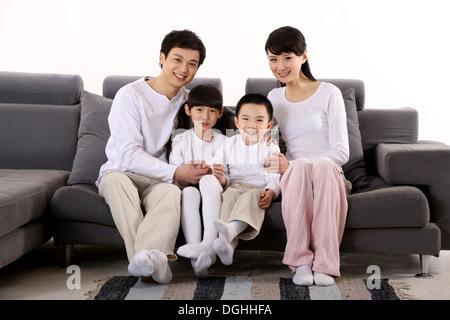 Ostasiatische Familie mit zwei Kindern, auf dem Sofa sitzen mit Lächeln in die Kamera schaut - Stockfoto