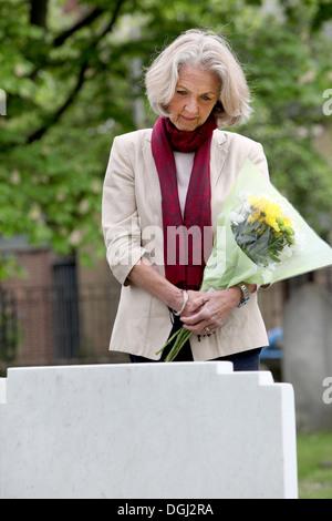 Ältere Frau mit Blumen auf Friedhof - Stockfoto