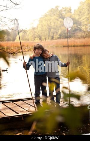 Brüder zusammenstehen auf Pier holding Fischernetze, Porträt - Stockfoto